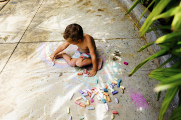 High angle view of boy drawing with chalk on footpath