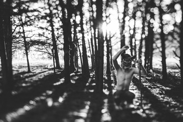 Full length of boy wearing mask while crouching on field in forest during Halloween