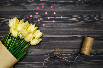 Spring background with bunch of tulip flowers corner with pink heart sprinkles on wood background, copy space. Flat lay. Greeting card for Valentine's Day, Woman's Day (March 8), Mother's Day, Easter