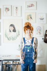 Portrait of smiling artist with hands in pockets standing in studio