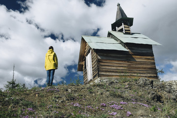 Rear view of mature woman standing by church on hill against cloudy sky