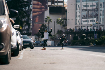 Male friends skateboarding on road in city during sunny day