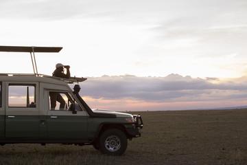 Side view of man looking through binoculars while standing in van