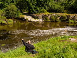 Cenarth, Pembrokeshire, Wales. July 1st 2017. Fisherman throwing his line on the river Teifi at Cenarth, Pembrokeshire, wales, UK