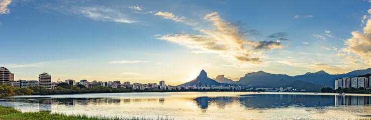 Panoramic image of the first summer sunset of the year 2018 seen from the lagoon Rodrigo de Freitas with the buildings of the city of Rio de Janeiro, hill Dois Irmãos and Gavea stone