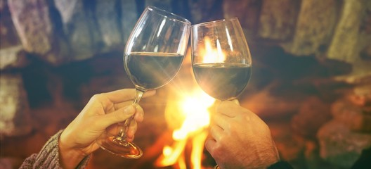Cropped image of hands toasting wineglasses against fireplace