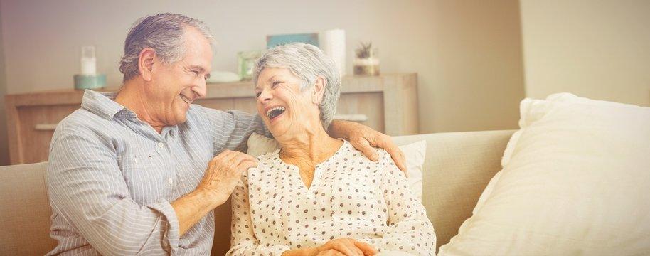 Romantic senior couple laughing while sitting on sofa