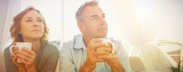 Thoughtful middle aged couple sitting on the couch having coffee
