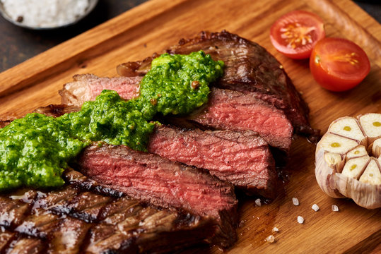 Grilled Black Angus Steak with tomatoes, garlic with chimichurri sauce on meat cutting board.