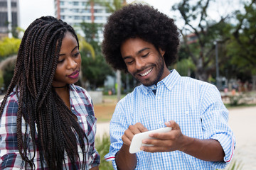 African american hipster man showing pictures at phone