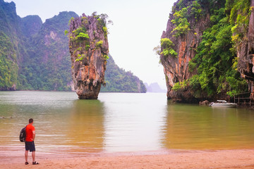 Tourist, a man, vatches James Bond Island, Phang Nga, Thailand, Asia. Monsoon, rainy wether landscape..