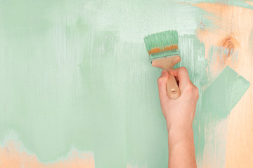 Men's hand paint wooden surface with green paint using a paint brush