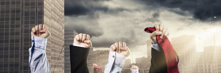 Fäuste von Geschäftsleuten erheben sich und demonstrieren vor Wolkenkratzer im Sonnenlicht