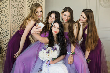 Bridesmaids taking a selfie on a smartphone and laugh during the morning of the bride at home. Beautiful girls in purple wedding dresses and bride with bouquet of peonies have fun. Preparation