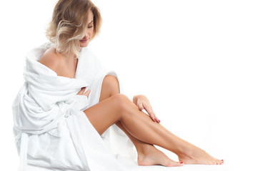 Beautiful girl in bathrobe is touching her legs. Depilation and bodycare concept