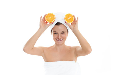 Beautiful young woman with clean fresh skin is holding two half oranges. Facial treatment