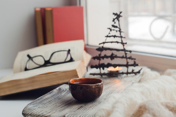 a cozy place to read on the windowsill - Asian tea, a warm scarf, a book, an atmosphere of coziness, inspiration, relaxation at home