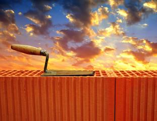Trowel on brick wall in sunset. Masonry tools.