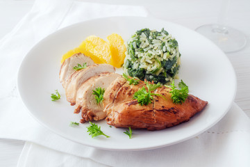 Chicken breast with orange fillets and spinach rice on a white plate, healthy diet dish with low calories