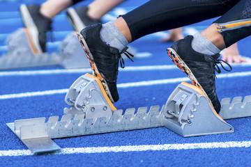 Sprintstart in der Leichtathletik auf blauer Tartanbahn