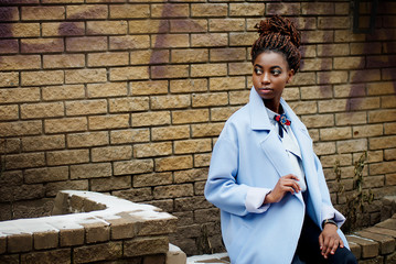 African girl in the blue coat in the style fashion sitting on the ledge and background the yellow brick wall