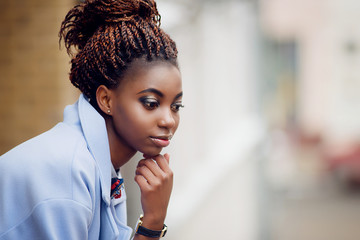 African girl with bright make-up looks down and thinks on the background of the street