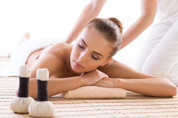 Young, beautiful and healthy woman relaxing in spa salon. Traditional oriental aroma therapy and massaging treatments