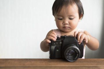 little asian toddler playing with old film camera (dslr). learning concept