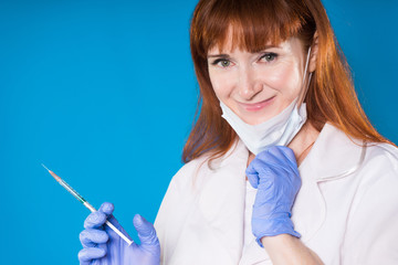 Beautiful doctor girl on a blue background holds a syringe and smiles, kind and sweet
