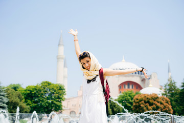 A young woman in a scarf with a backpack on the background of Aya Sofia and a fountain, hands up. Summer vacation, traveler, Turkey