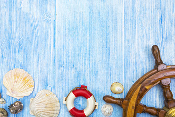 Maritime blue weathered wood background with helm, lifebuoy, shells, copy space in top half