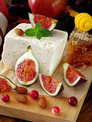 Cheese made of sheep milk and slices of figs on a wooden board surrounded by cranberries, honey and almond