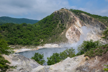 The hot water of Oyunuma pond in the volcanic landscape of Hell Valley (Jigokudani), Noboribetsu, Hokkaido, Japan