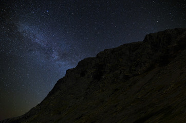 Night starry sky. The Milky Way in the background of a mountain range.
