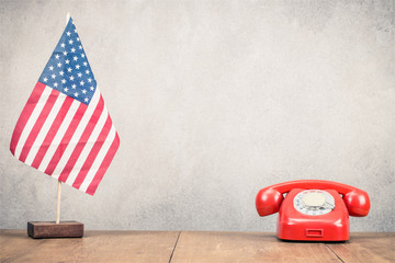 USA flag and retro red classic rotary telephone on wooden desk front old concrete wall background. Vintage style filtered photo
