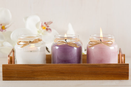 White, purple and pink candles on wooden tray