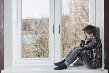 Crying young boy sitting alone in window and hide his face in hands.