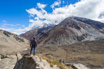 Man standing on rock and looking on mountains. Annapurna circle trekking, Nepal. Back view.
