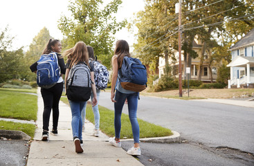 Four young teen girls walking to school together, back view Fototapete