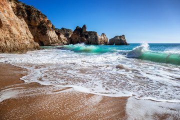 Algarve, Portugal, a stunning sea ocean landscape with yellow rocks and azure water. The beauty of nature and the power of the ocean