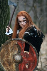 Warrior woman, viking with ax and shield, in the forest