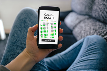 Girl holding smart phone with online tickets concept on screen. All screen content is designed by me