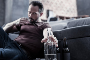 I need it. Unhappy cheerless brutal man sitting on the floor and reaching for the bottle while being addicted to alcohol