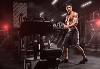 A young handsome, inflated man, equips a machine for exercise. Training for the feet, on a beautiful background, in a modern sports club.