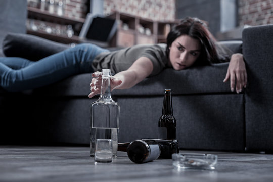 I need this drink. Selective focus of a half empty vodka bottle being taken by a drunken young woman while having a hangover