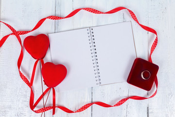 Valentines day toy hearts and notepad for your text. Top view on wooden table