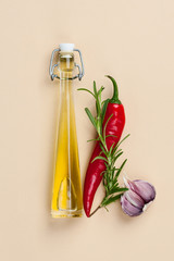 Olive oil, chili pepper, rosemary and garlic on a light beige background..