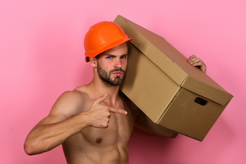 Man with beard stands on pink background, points to box.