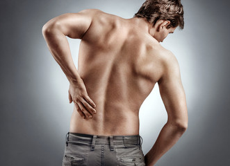 Man holding his back in pain on grey background. Medical concept
