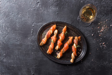 Spoed Fotobehang Voorgerecht Appetizer with smoked salmon on crispy breadsticks served on vintage metal tray with sea salt, glass of white wine over black texture background. Top view with space